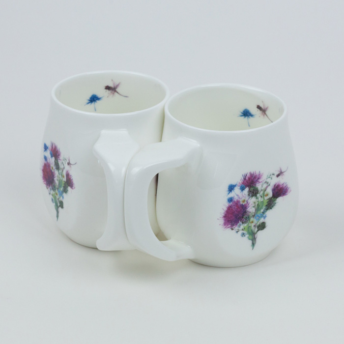 A pair of white fine bone china mugs with a colourful dragonfly printed on the side.