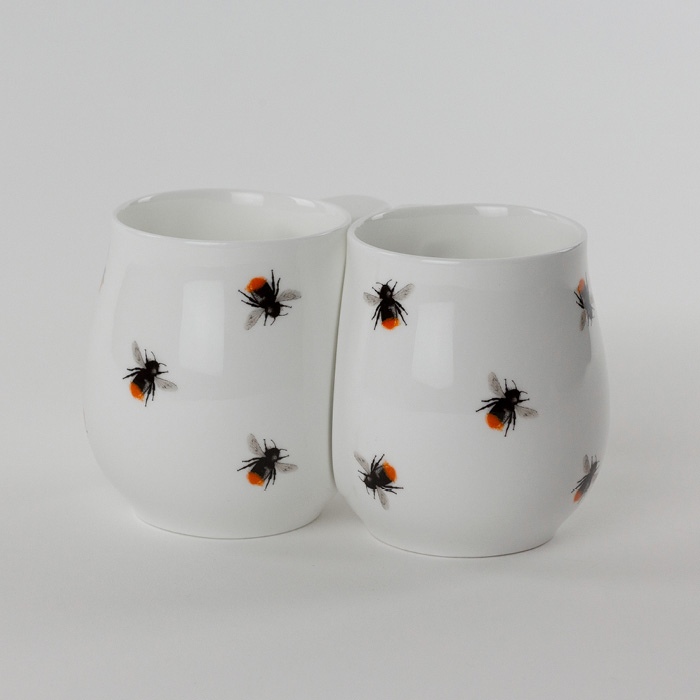 Two white fine bone china mugs with a colourful red bee printed on the side.
