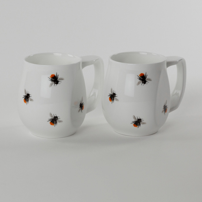 A pair of white fine bone china mugs with a colourful red bee printed on the side.